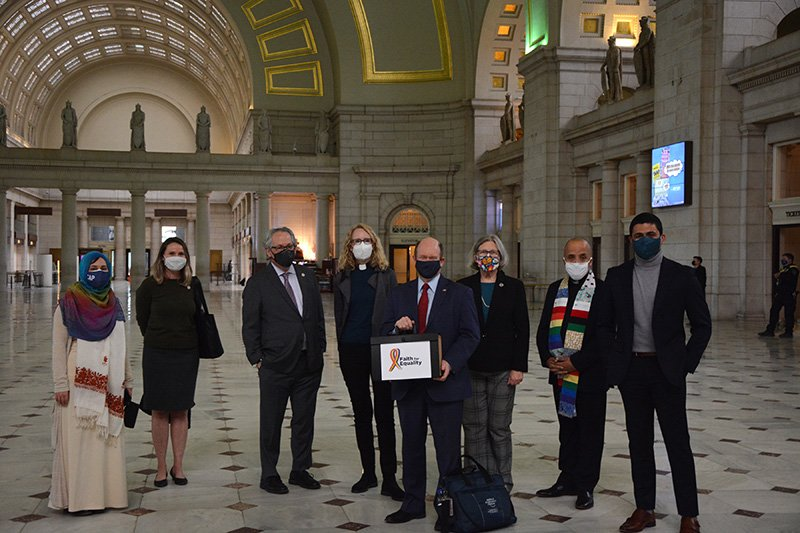 Sen. Chris Coons (D-DE), center, accepts a group of petitions from faith leaders in support of the Equality Act, Tuesday, March 16, 2021, in Washington D.C.'s Union Station. RNS photo by Jack Jenkins