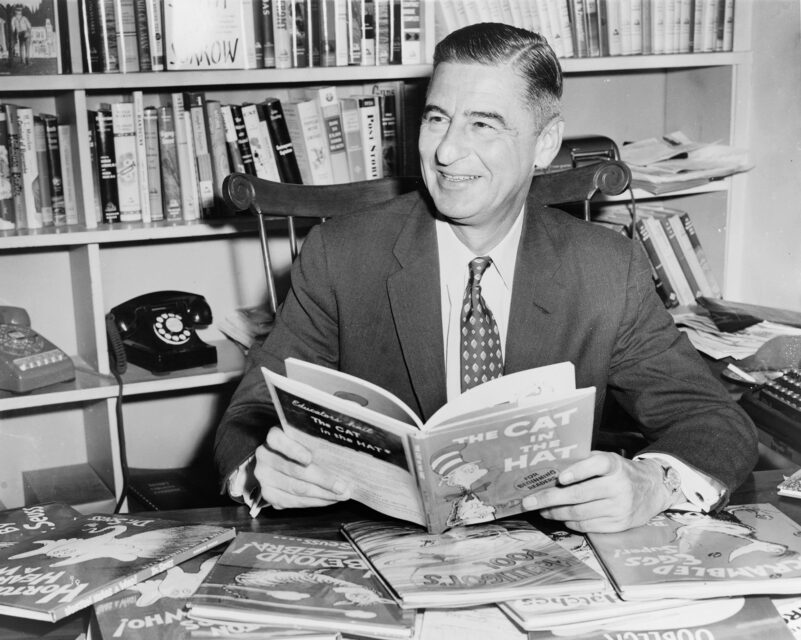 Ted Geisel (Dr. Seuss) sits at a desk covered with his books in 1957. Photo by Al Ravenna/World Telegram & Sun/LOC/Creative Commons