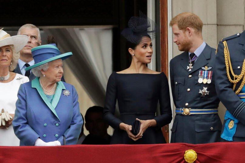 In this July 10, 2018, file photo, Britain's Queen Elizabeth II, from left, Meghan the Duchess of Sussex and Prince Harry stand on a balcony to watch a flypast of Royal Air Force aircraft pass over Buckingham Palace in London. The Duke and Duchess of Sussex told the story behind their departure from royal duties directly to the public on Sunday, March 7, 2021, when their two-hour interview with Oprah Winfrey was broadcast. (AP Photo/Matt Dunham, File)