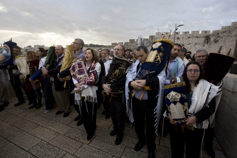 In this Nov. 2, 2016, file photo, leaders of the Jewish Reform and Conservative movements carry Torah scrolls as they march to the Western Wall, the holiest site where Jews can pray in Jerusalem's Old City. Israel's Supreme Court on Monday, March 1, 2021, dealt a major blow to the country's powerful Orthodox establishment, ruling that people who convert to Judaism through the Reform and Conservative movements in Israel also are Jewish and entitled to become citizens. (AP Photo/Sebastian Scheiner, File)