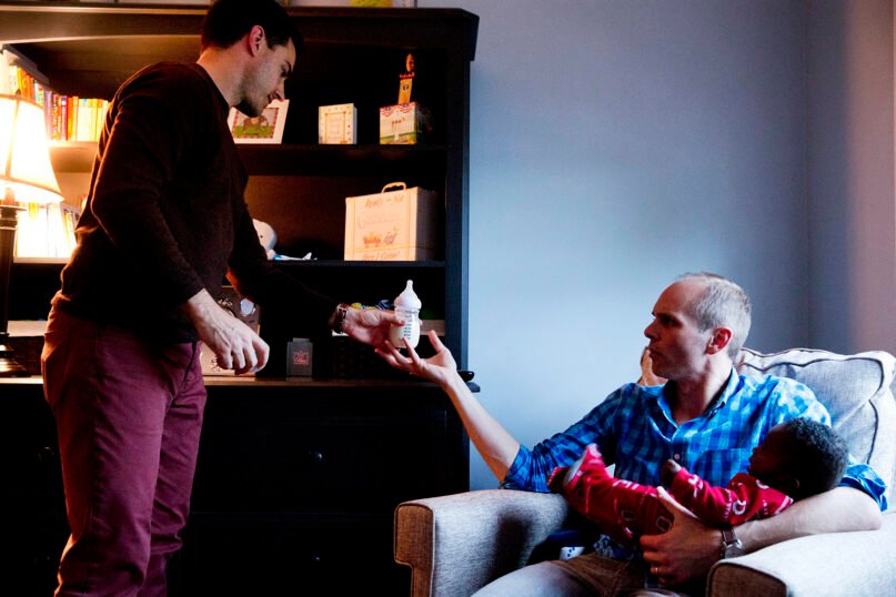 Brooks Brunson, left, passes a bottle of formula to his husband, Gregg Pitts, as they prepare their son, Thomas Brunson-Pitts, 6 months old, for bed at their home in Washington on Wednesday, May 4, 2016. Originally from Texas and Ohio, they were married in the District of Columbia in November 2013. Brunson and Pitts always knew they wanted to have a family together and were delighted when they were able to start the adoption process for their son shortly after beginning to look for a match in 2015. (AP Photo/Jacquelyn Martin)