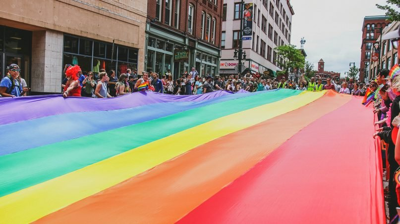 Marchers carry a large rainbow flag down Congress Street during the annual Pride parade in Portland, Maine. Photo by Mercedes Mehling/Unsplash/Creative Commons