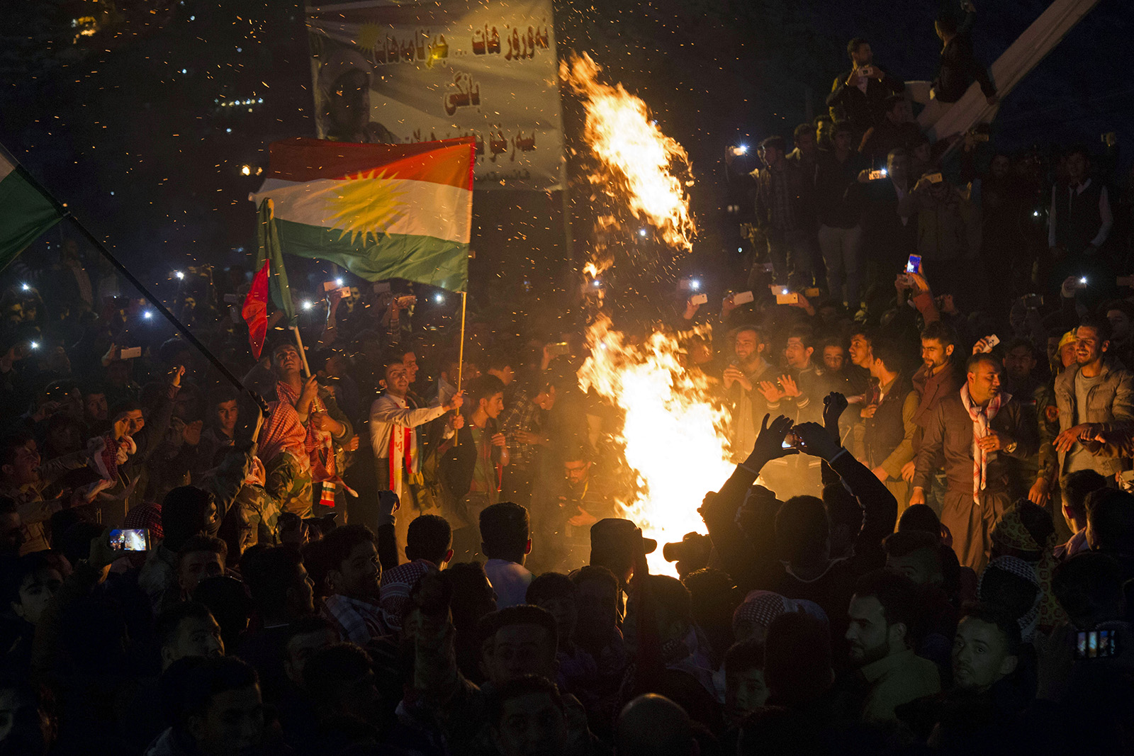 """Kurdish men and women gather around a fire during celebrations for Nowruz, in Akre, Iraq. Nowruz, the Farsi-language word for """"new year,"""" is an ancient Persian festival, celebrated on the first day of spring in countries including Afghanistan and Iran. (AP Photo/Seivan M.Salim)"""