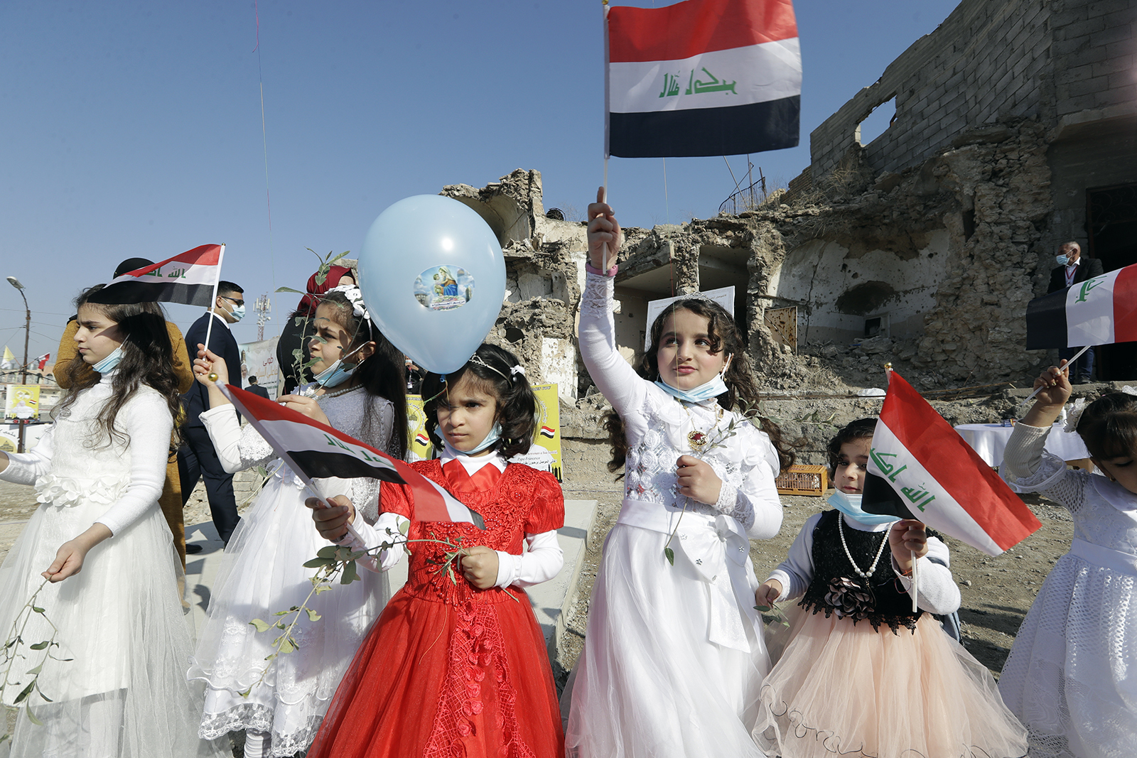 Children in festive garments wave Iraqi flags to the camera as they await the arrival of Pope Francis, who prayed for victims of war at Hosh al-Bieaa Church Square, in Mosul, Iraq, once the de-facto capital of IS, Sunday, March 7, 2021. (AP Photo/Andrew Medichini)
