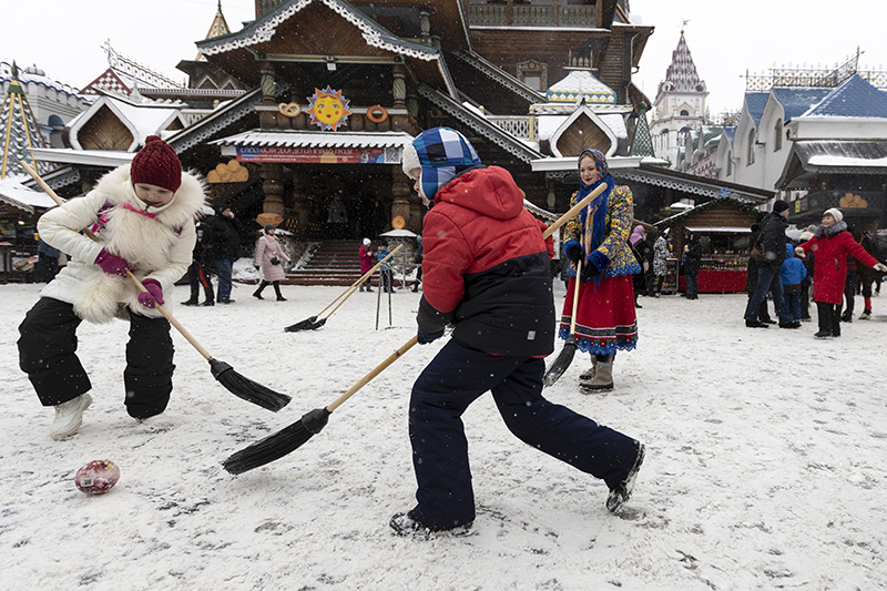 Children play ball with brooms during Maslenitsa (Shrovetide) holiday celebrations at the Izmailovsky Kremlin in Moscow, Russia, Saturday, March 13, 2021. Maslenitsa is an Orthodox Christian holiday celebrated in the last week before the Orthodox Lent. The festivities feature baking traditional pancakes, sleigh rides, sparring between groups of men and, finally burning the effigy of Maslenitsa. (AP Photo/Alexander Zemlianichenko)