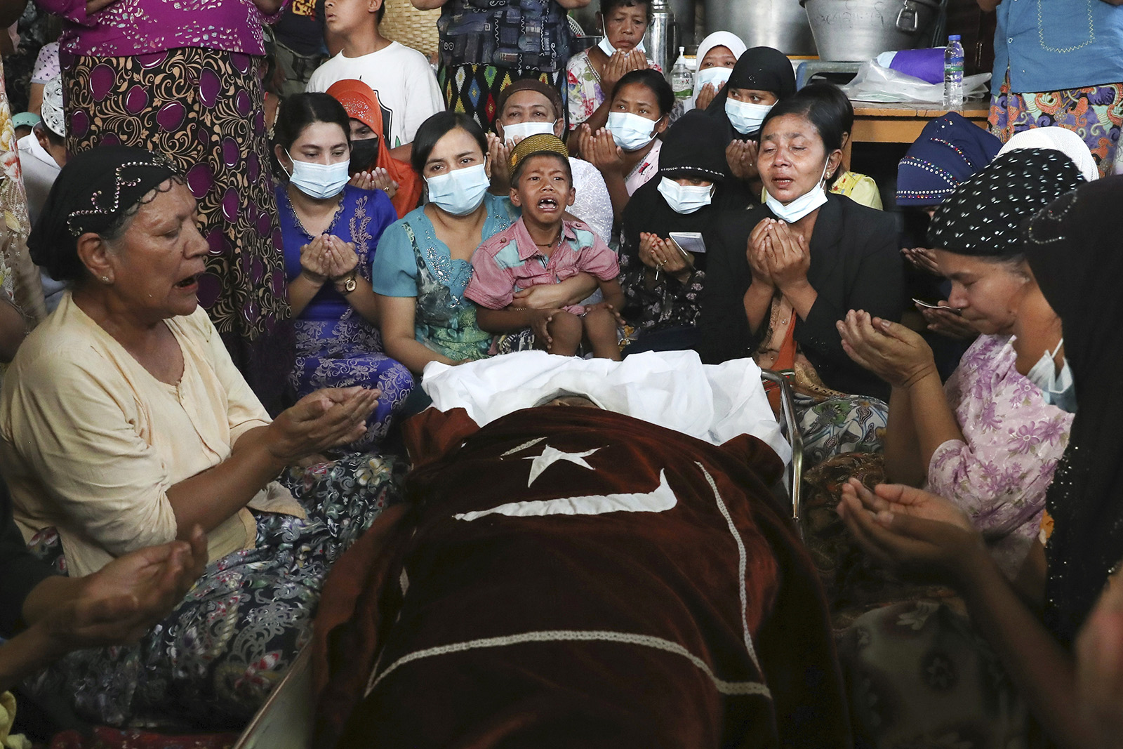 Family and relatives pray next to the body of a Muslim woman, who her family said was killed by the army Sunday, during her funeral service in Mandalay, Myanmar, Monday, March 1, 2021. Defiant crowds returned to the streets of Myanmar's biggest city of Yangon on Monday, determined to continue their protests against the military's seizure of power a month ago, despite security forces having killed at least 18 people around the country just a day earlier. (AP Photo)