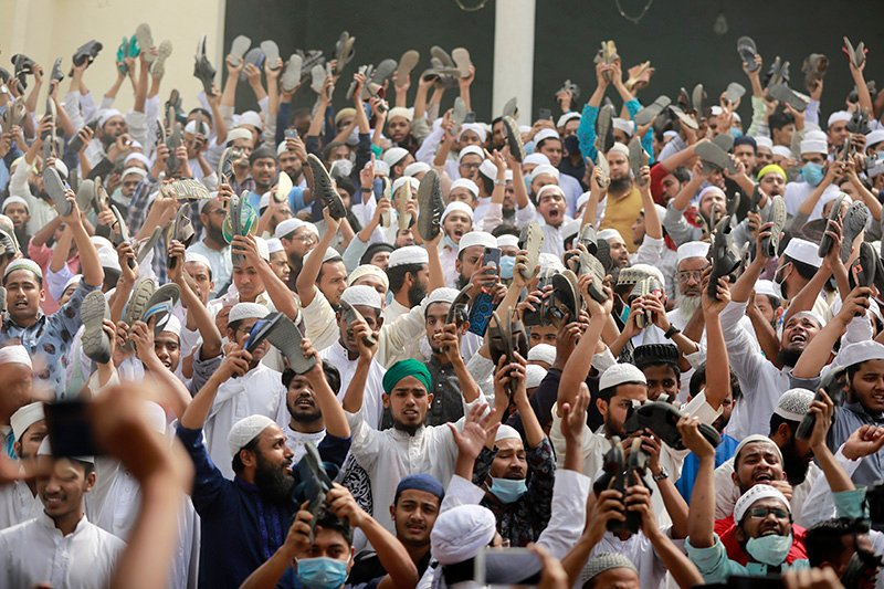 Bangladeshi Muslims raise their footwear and shout slogans during a protest after Friday prayers, against the visit of Indian Prime Minister Narendra Modi in Dhaka, Bangladesh, Friday, March 19, 2021. Hundreds of people including Muslim devotees and left-leaning student activists on Friday rallied in Bangladesh's capital to denounce the upcoming visit of Indian Prime Minister Narendra Modi to join the celebration of the country's 50th anniversary of independence. (AP Photo/Al-emrun Garjon)