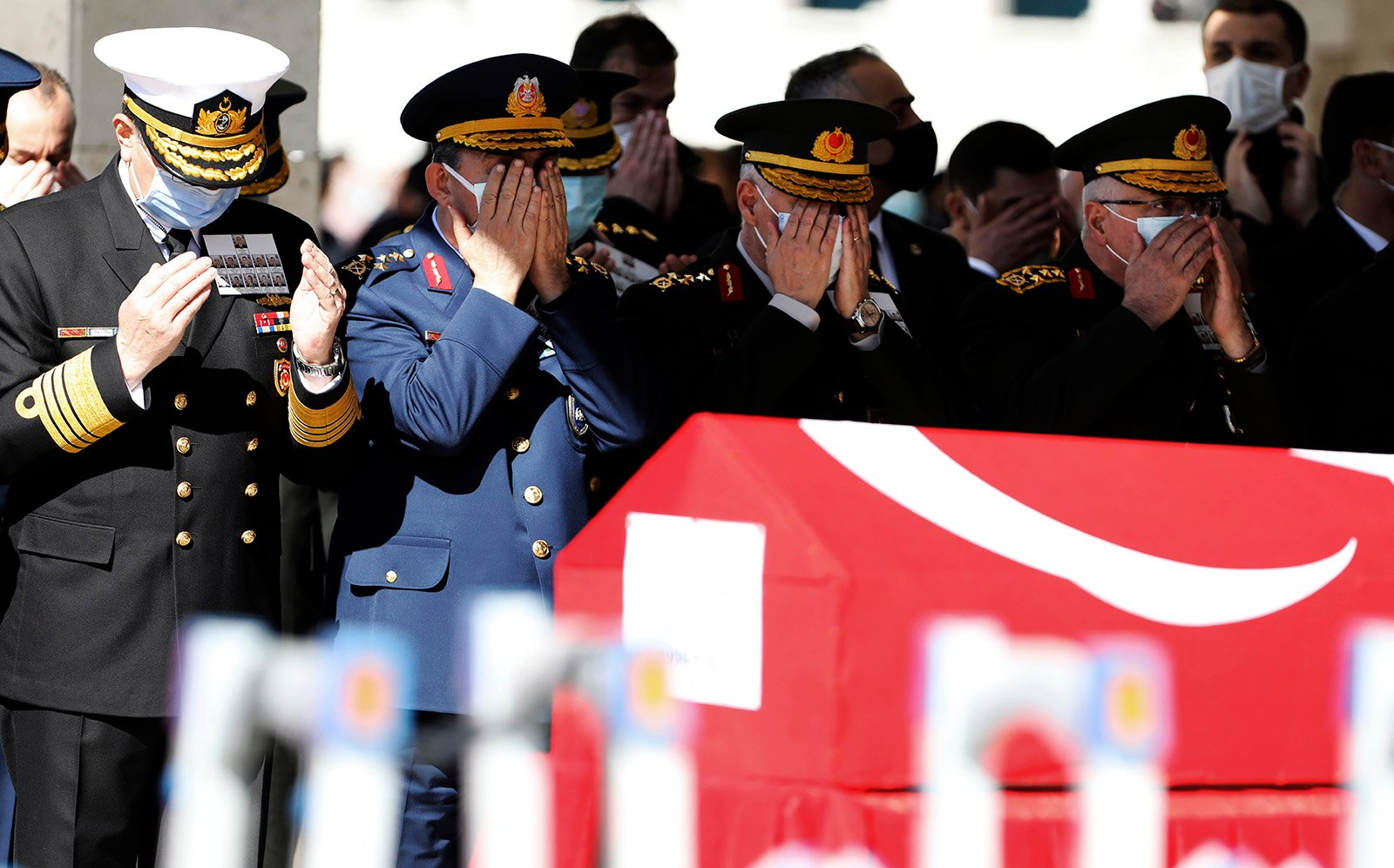Turkish army commanders pray as Turkish leaders, army commanders, family members and colleagues attend funeral prayers and a ceremony for 11 military personnel, including a high-ranking officer, at Ahmet Hamdi Akseki Mosque, in Ankara, Turkey, Friday, March 5, 2021. Turkish army officers were killed on Thursday when an army helicopter crashed in a snow-covered mountainous area in Bitlis, eastern Turkey. (AP Photo/Burhan Ozbilici)