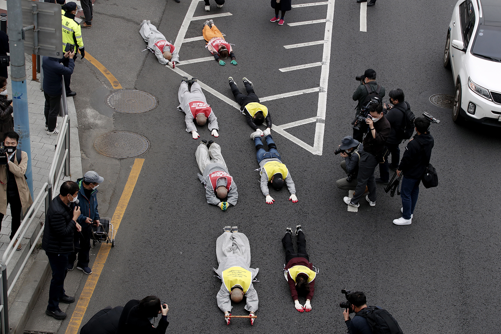 South Korean Buddhist monks and Myanmar people living in South Korea prostrate on the road during a protest calling for the recovery of Myanmar's democracy and against the military coup near the Myanmar embassy in Seoul, South Korea, Friday, March 12, 2021. (AP Photo/Lee Jin-man)