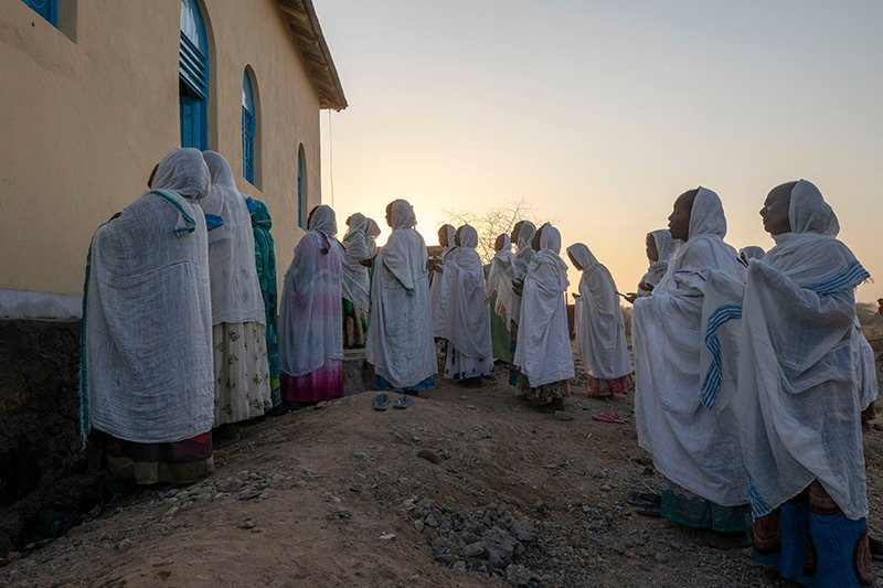 Orthodox Christian Tigrayan refugees who fled the conflict in the Ethiopia's Tigray state pray in front of a church at Hamdeyat Transition Center near the Sudan-Ethiopia border, eastern Sudan, Tuesday March 16, 2021. (AP Photo/Nariman El-Mofty)