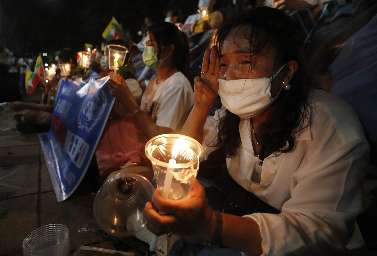 Myanmar nationals living in Thailand gesture with a three-finger sign of resistance during a candlelight vigil against the Myanmar military coup in front of the United Nations building in Bangkok, Thailand, Thursday, March 4, 2021. (AP Photo/Sakchai Lalit)