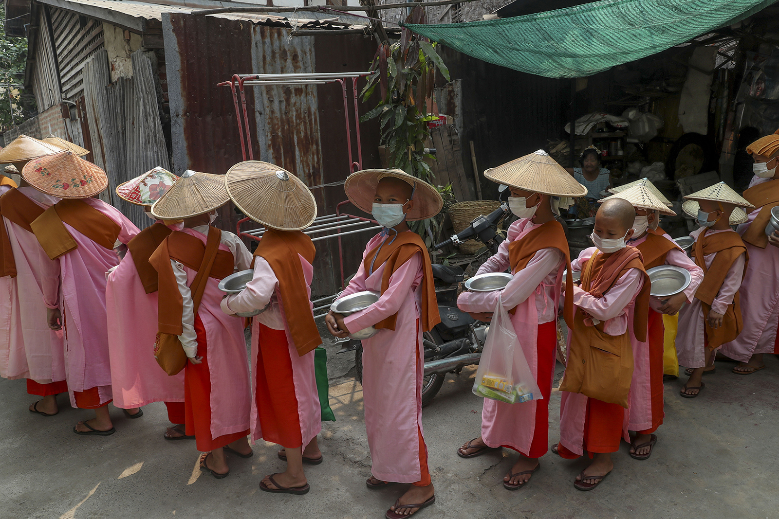 """Buddhist nuns collect alms, or offerings, in Mandalay, Myanmar, Thursday, March 11, 2021. The U.N. Security Council unanimously called for a reversal of the military coup in Myanmar on Wednesday, strongly condemning the violence against peaceful protesters and calling for """"utmost restraint"""" by the military. (AP Photo)"""