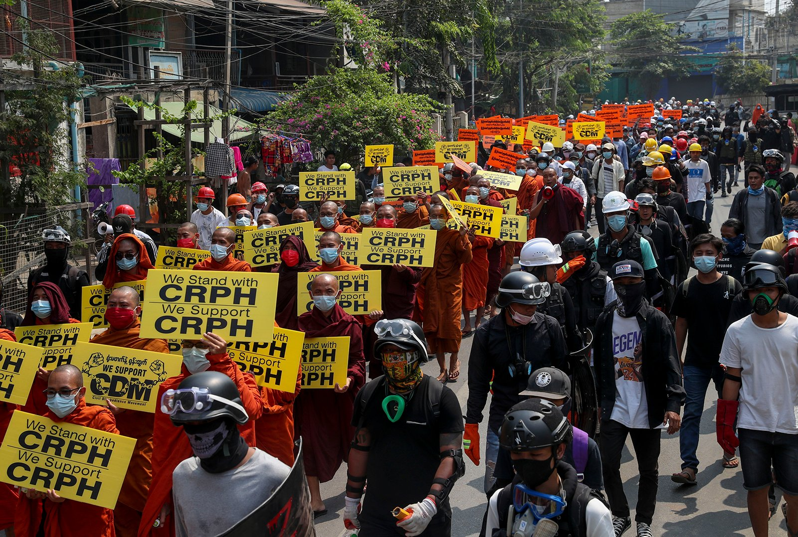 Buddhist monks, supporters of anti-coup protesters, display placards with the letters CRPH standing for Committee Representing elected members of the Union Parliament from the National League for Democracy Party, during a street march in Mandalay, Myanmar, Wednesday, March 10, 2021. (AP Photo)