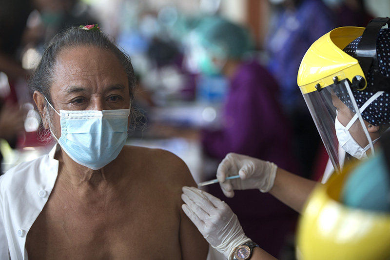 A Hindu priest receives a shot of Sinovac COVID-19 vaccine during a vaccination for various religious leaders in Denpasar, Bali, Indonesia on Tuesday, March 16, 2021. (AP Photo/Firdia Lisnawati)