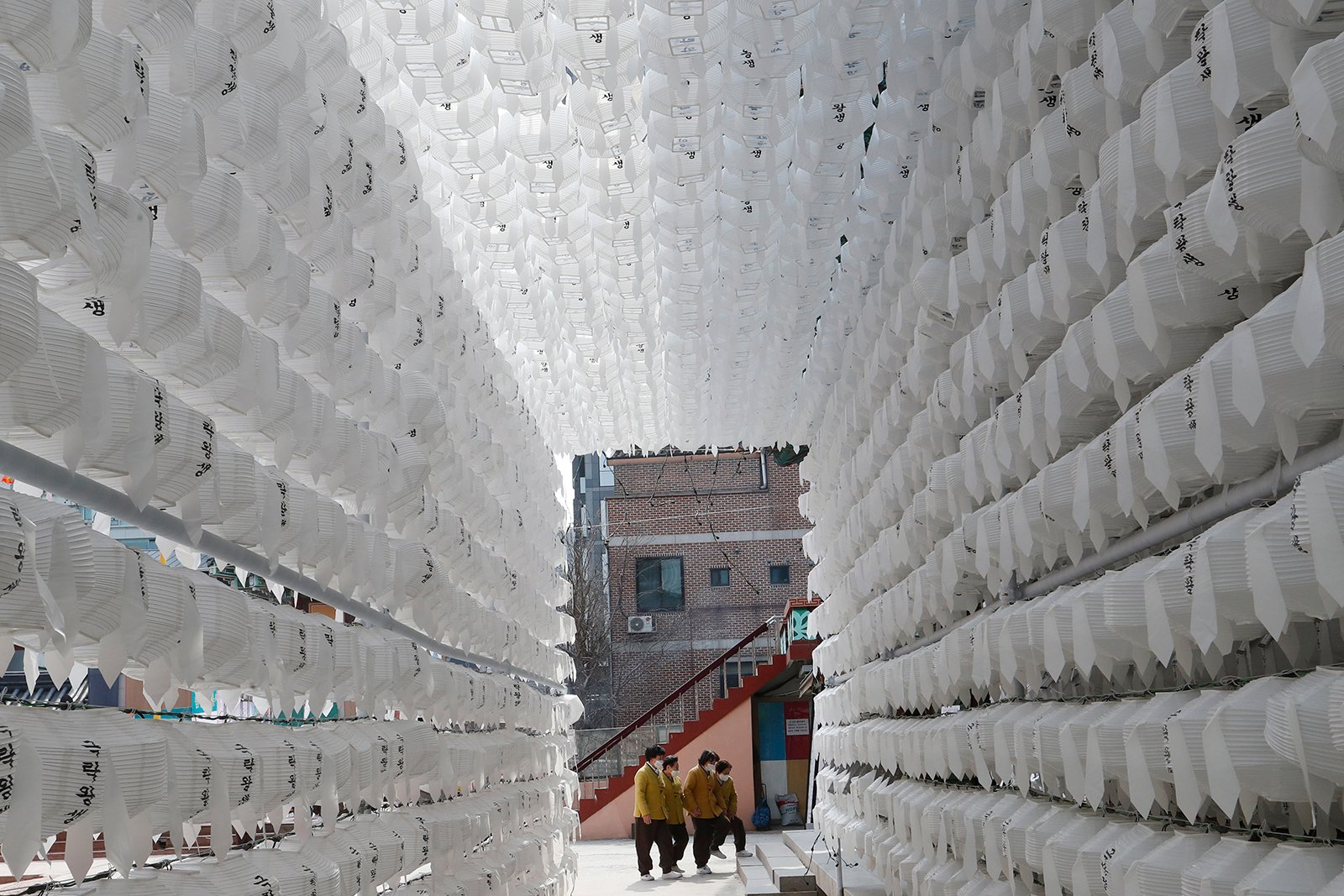 People pass by lanterns for the upcoming celebration of Buddha's birthday (May 19) at Jogyesa temple in Seoul, South Korea, Tuesday, March 9, 2021. (AP Photo/Ahn Young-joon)