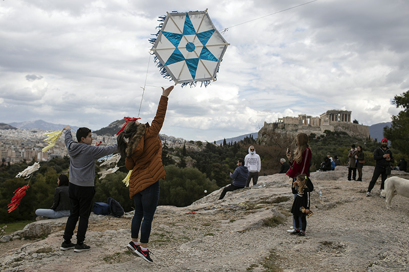 People fly kites near the ancient Parthenon temple in Athens, background, on Clean Monday, March 15, 2021. The coronavirus pandemic, which hit Greece especially hard this winter, threatened to ground the annual kite-flying tradition, an essential part of the celebration of Clean Monday, the first day of Orthodox Lent. (AP Photo/Petros Giannakouris)