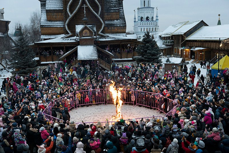 People watch as an effigy of Lady Winter burns during Maslenitsa (Shrovetide) holiday celebrations at the Izmailovsky Kremlin in Moscow, Russia, Saturday, March 13, 2021. Maslenitsa is an Orthodox Christian holiday celebrated in the last week before the Orthodox Lent. The festivities feature baking traditional pancakes, sleigh rides, sparring between groups of men and, finally burning the effigy of Maslenitsa. (AP Photo/Alexander Zemlianichenko)