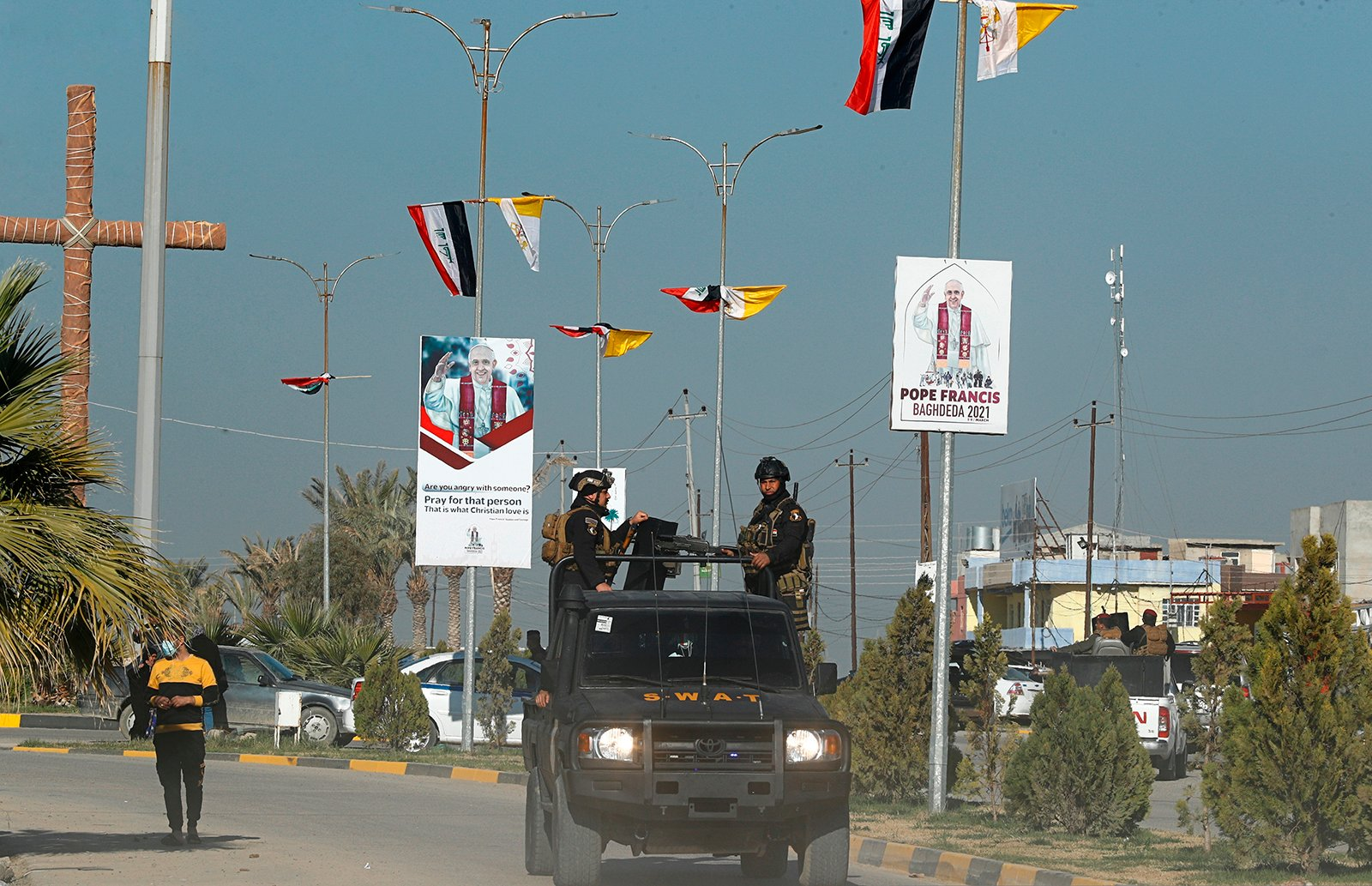 Iraqi security forces pass by Iraqi and the Vatican flags, and posters announcing the upcoming visit of Pope Francis, in a street in Qaraqosh, Iraq, Monday, Feb. 22, 2021. (AP/Photo/Hadi Mizban)