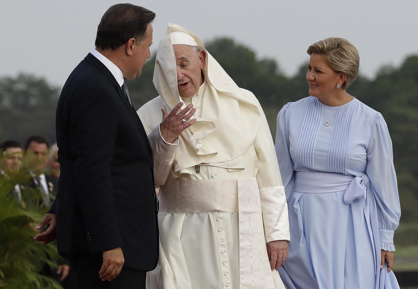 The wind blows Pope Francis' mantle as he speaks with Panamanian President Juan Carlos Varela and first lady Lorena Castillo de Varela after landing at Tocumen international airport in Panama City, Wednesday, Jan. 23, 2019. (AP Photo/Alessandra Tarantino)