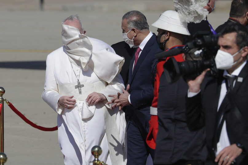 A gust of wind blows Pope Francis' mantle as he stands by Iraqi Prime Minister Mustafa al-Kadhimi upon the pope's arrival at Baghdad's international airport on March 5, 2021. (AP Photo/Andrew Medichini)