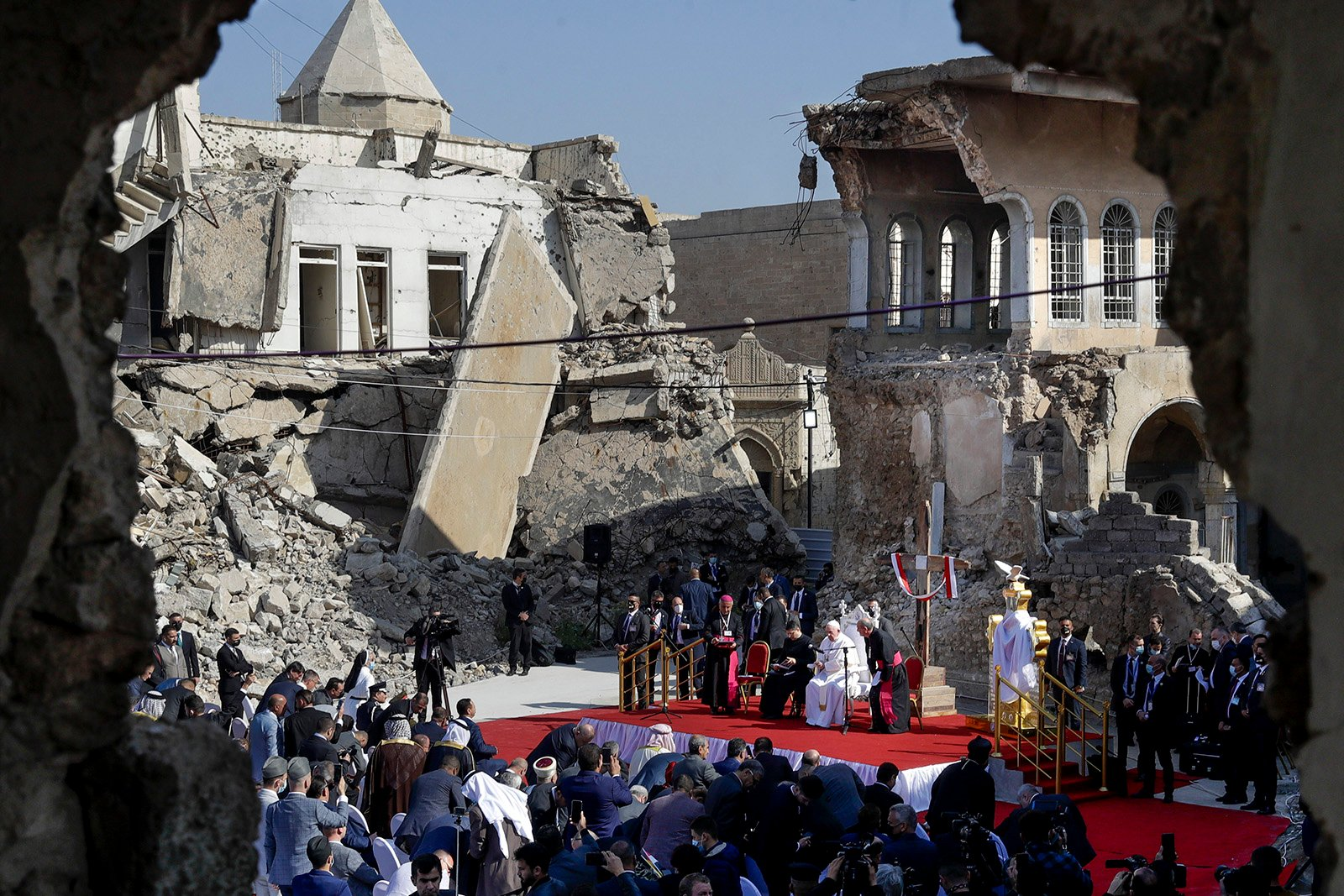 Pope Francis, surrounded by shells of destroyed churches, leads a prayer for the victims of war at Hosh al-Bieaa Church Square, in Mosul, Iraq, once the de-facto capital of ISIS, Sunday, March 7, 2021. The long 2014-2017 war to drive ISIS out left ransacked homes and charred or pulverized buildings around the north of Iraq, all sites Francis visited on Sunday. (AP Photo/Andrew Medichini)