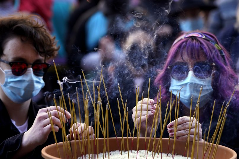 People leave incense sticks in a pot of rice to honor the eight victims of the Atlanta area spa shootings during a memorial in Kansas City, Missouri, on March 28, 2021. (AP Photo/Charlie Riedel)