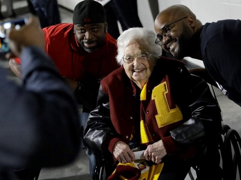 Loyola-Chicago basketball chaplain Sister Jean Dolores Schmidt, center, poses with fans for a photo before the first half of a regional final NCAA college basketball tournament game, Saturday, March 24, 2018, in Atlanta. (AP Photo/David Goldman)