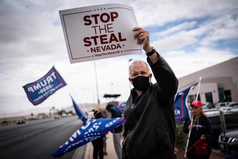 Supporters of President Donald Trump hold signs as they stand outside of the Clark County Elections Department in North Las Vegas, Nev., Saturday, Nov. 7, 2020. (AP Photo/Wong Maye-E)