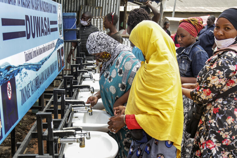 FILE - In this Monday, May 18, 2020, file photo, people use a hand-washing station installed for members of the public entering a market in Dodoma, Tanzania. Tanzania's COVID-denying president John Magufuli, on Friday Feb. 19, 2021, called on citizens for three days of prayer to defeat unnamed