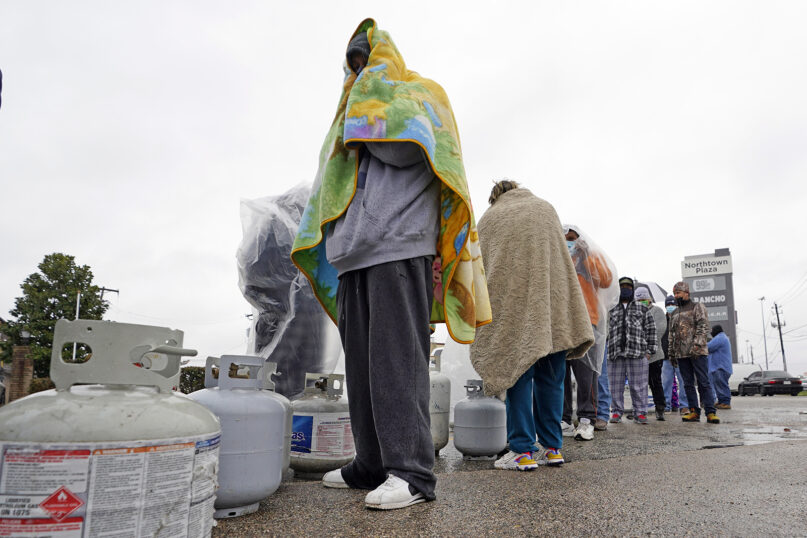 Carlos Mandez, center, waits in line to fill his propane tanks Wednesday, Feb. 17, 2021, in Houston. Customers had to wait over an hour in the freezing rain to fill their tanks. A recent historic snowfall and single-digit temperatures created a surge of demand for electricity to warm up homes unaccustomed to such extreme lows, buckling the state's power grid and causing widespread blackouts. (AP Photo/David J. Phillip)