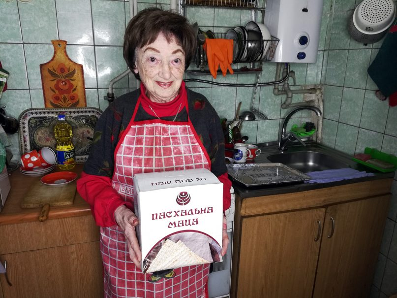 Nina Belitskaya, an 89-year-old retired librarian, holds the matzo box she received from JDC this year in Poltava, Ukraine. Tens of thousands of elderly Jews in the region receive matzo boxes from JDC for the Passover holiday. Photo courtesy of JDC