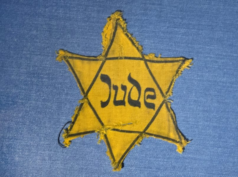 FILE - In this Wednesday, Jan. 22, 2014 file photo, the Yellow Star badge of Heinz-Joachim Aris (Dresden 1941) reading 'Jew' is displayed in a showcase during a press preview in the new special exhibition 'Shoes of the Dead - Dresden and the Shoah' at the Military History Museum in Dresden, Germany. (AP Photo/Jens Meyer, file)