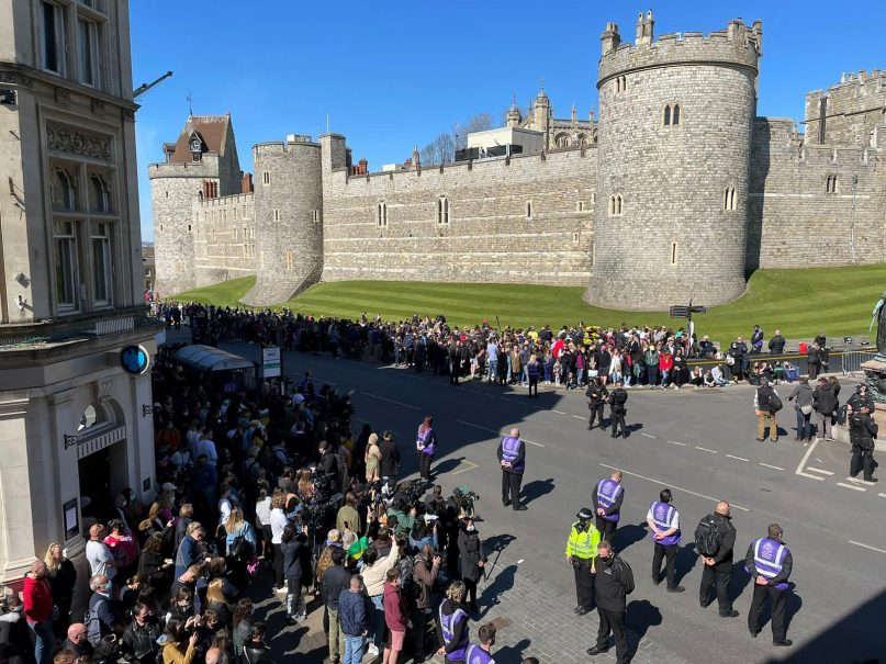 People gather outside Windsor Castle during the funeral of Britain's Prince Philip in Windsor, England, on April 17, 2021. Philip died April 9 at the age of 99 after 73 years of marriage to Britain's Queen Elizabeth II. (AP Photo/Stefan Cottrell)