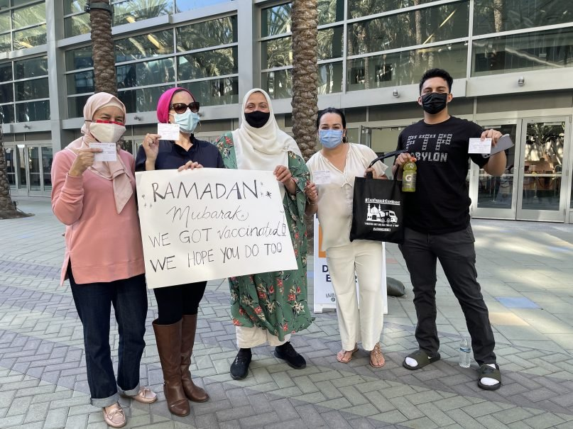"""A group of Muslims display their vaccination cards and a sign reading """"Ramadan Mubarak: We got vaccinated. We hope you do too,"""" on Sunday, April 11, 2021, at the Anaheim Convention Center in Anaheim, California. Rida Hamida, second from left, is the executive director of Latino & Muslim Unity. Photo courtesy of Latino & Muslim Unity"""