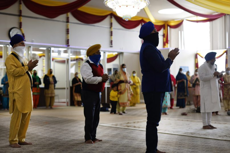 Sikhs pray during Vaisakhi celebrations at Guru Nanak Darbar of Long Island, Tuesday, April 13, 2021 in Hicksville, N.Y. Sikhs across the United States are holding toned-down Vaisakhi celebrations this week, joining people of other faiths in observing major holidays cautiously this spring as COVID-19 keeps an uneven hold on the country. (AP Photo/Jason DeCrow)