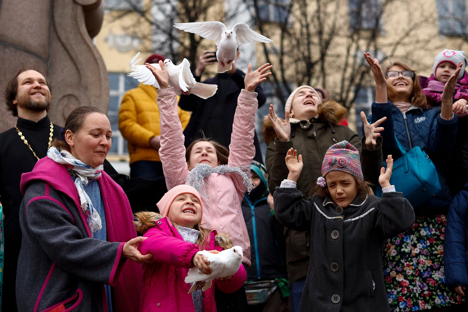 Children and their parents release birds celebrating the Annunciation on the eve of Orthodox Easter in front of the St. Tatiana Church in Moscow, Russia, Wednesday, April 7, 2021. Eastern Orthodox churches, which observe the ancient Julian calendar, usually celebrate Easter later then Western churches. (AP Photo/Alexander Zemlianichenko)