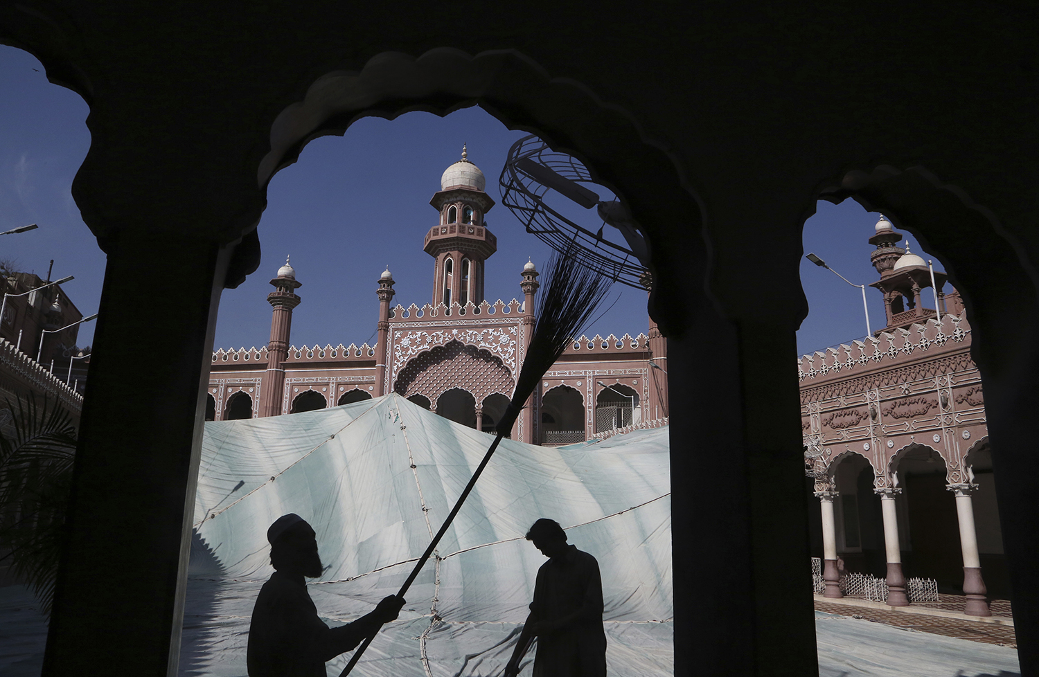 Volunteers clean the outer areas of a historical Mohabat Khan mosque ahead of the upcoming Muslim fasting month of Ramadan, in Peshawar, Pakistan, Friday, April 9, 2021. (AP Photo/Muhammad Sajjad)