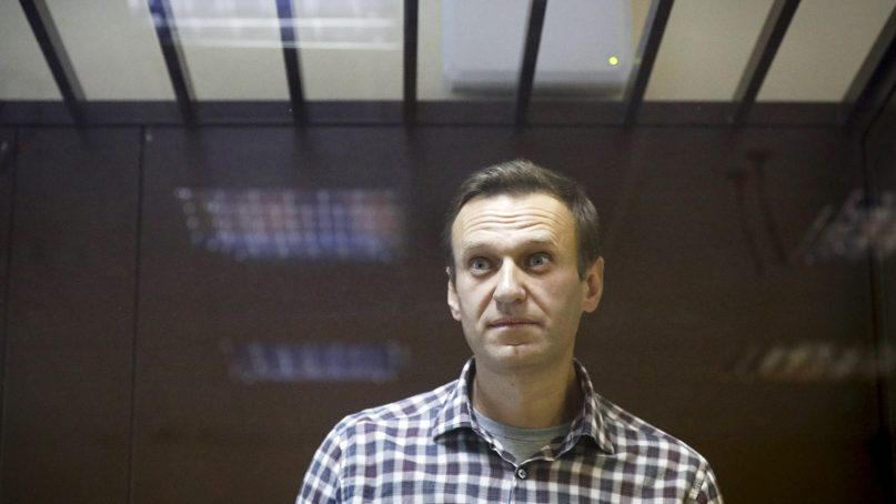 In this Saturday, Feb. 20, 2021 file photo, Russian opposition leader Alexei Navalny stands in a cage in the Babuskinsky District Court in Moscow, Russia.  (AP Photo/Alexander Zemlianichenko, File)