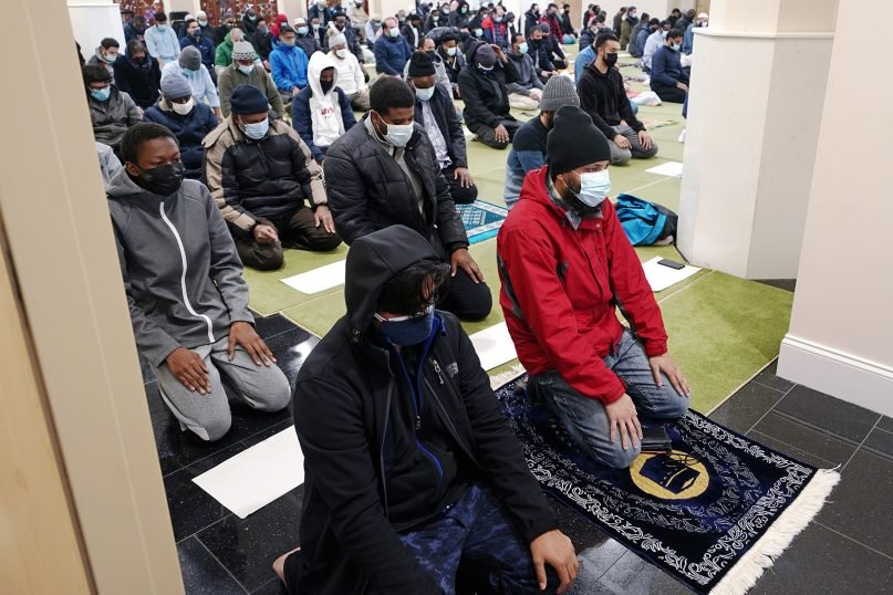 Worshippers, wearing masks and socially distanced due to COVID-19 concerns, kneel in prayer in the mosque of the Islamic Society of Boston during the first Friday of the holy month of Ramadan, April 16, 2021, in Boston. (AP Photo/Charles Krupa)