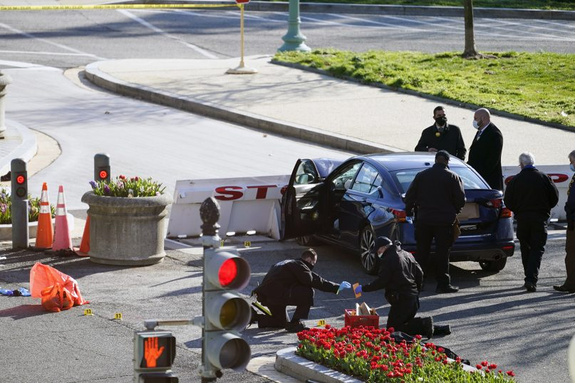 Authorities investigate the scene after a man rammed a car into two officers at the barricade on Capitol Hill in Washington, April 2, 2021. (AP Photo/Alex Brandon)
