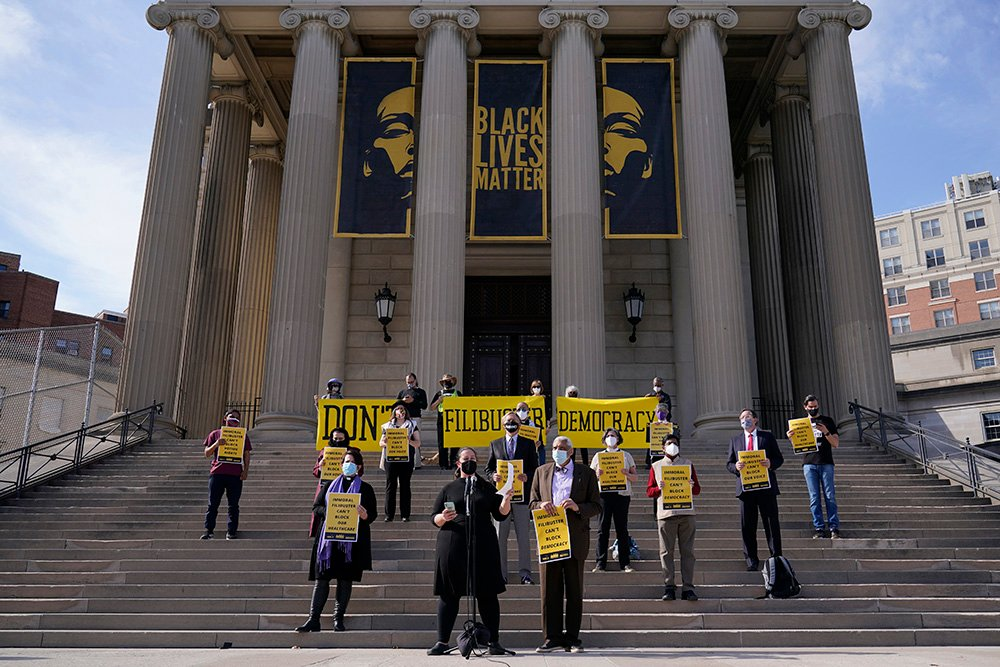 The Rev. Liz Theoharis, center at microphone, co-director of The Poor People's Campaign, speak outside National City Christian Church in Washington, Monday, April 5, 2021. A coalition of interfaith leaders and activists met in Washington and online to demand an end to the filibuster, calling it an arcane and racist tactic that blocks the passing of moral policies. (AP Photo/Susan Walsh)