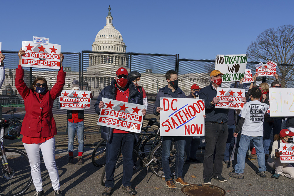 Advocates for statehood for the District of Columbia rally near the Capitol prior to a House of Representatives hearing on creating a fifty-first state, in Washington, Monday, March 22, 2021. The activists were able to gather near the Capitol building after the outer perimeter security fencing was dismantled this weekend. (AP Photo/J. Scott Applewhite)