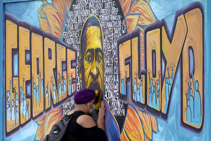 Damarra Atkins pays her respects to George Floyd at a mural at George Floyd Square on April 23, 2021, in Minneapolis. (AP Photo/Julio Cortez)