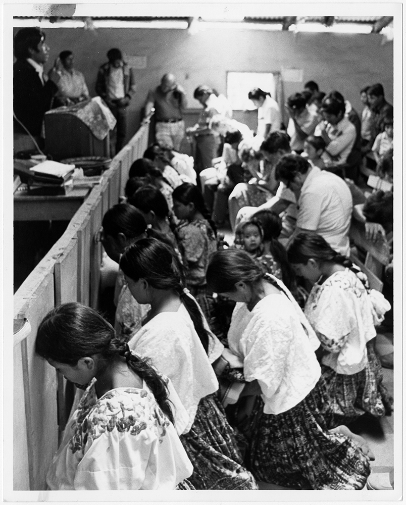 K'ekchi Indian women kneel as they pray for the sick following a morning worship service at Jerusalem Baptist Church in the Pocola Valley of Guatemala, in March 1980. Joining in the service (in background) are several participants from the Southern Baptist-sponsored seminar on work with indigenous people which metin nearby Coban. Jerusalem Baptist Church was one of two congregations in the late 1960s from which Baptist work among the K'ekchis grew to more than 67 congregations. RNS archive photo by Leland F. Webb. Photo courtesy of the Presbyterian Historical Society.