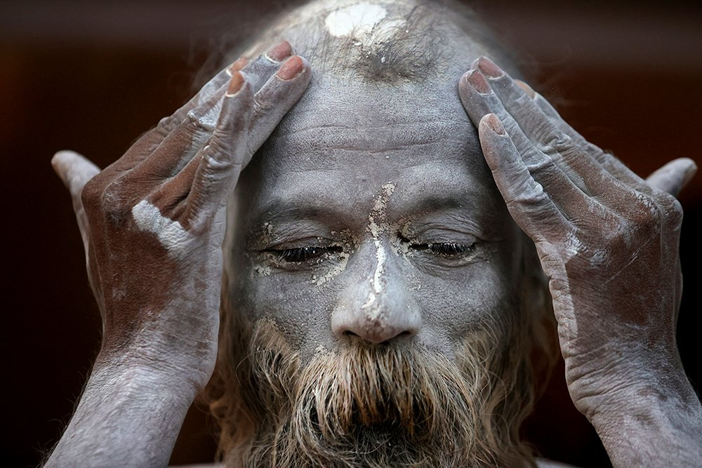 A Naga Sadhu, or Naked Hindu holy man, rubs ash as he prepares to take holy dips in the river Ganges during Shahi snan, or a Royal bath during Kumbh mela, in Haridwar in the Indian state of Uttarakhand, Monday, April 12, 2021. As states across India are declaring some version of a lockdown to battle rising Covid cases as part of a nationwide second-wave, thousands of pilgrims are gathering on the banks of the river Ganga for the Hindu festival Kumbh Mela. The faithful believe that a dip in the waters of the Ganga will absolve them of their sins and deliver them from the cycle of birth and death. (AP Photo/Karma Sonam)