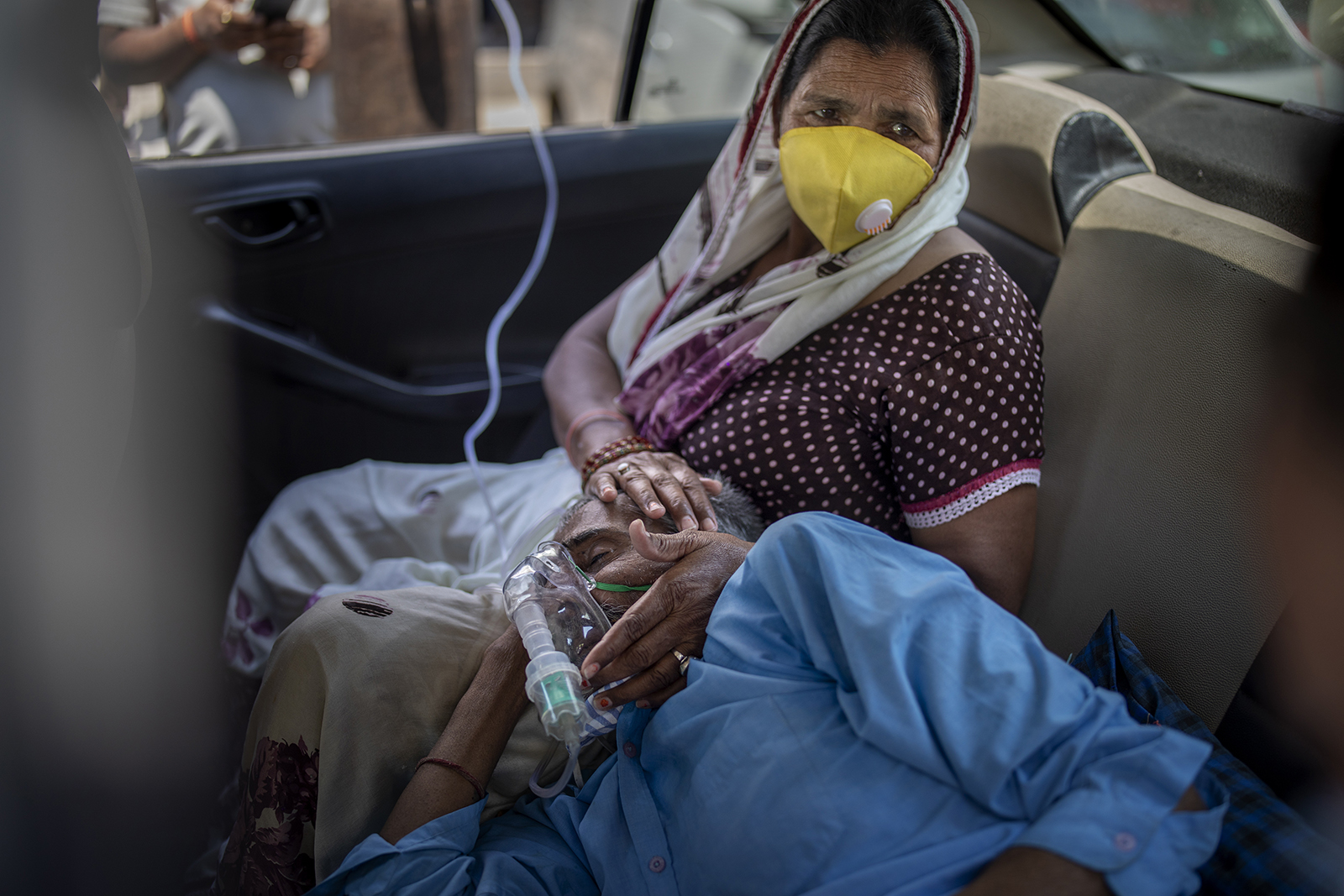 A patient breathes with the help of oxygen provided by a gurdwara, a Sikh house of worship, inside a car in New Delhi on April 24, 2021. India's medical oxygen shortage has become so dire that this gurdwara began offering free breathing sessions with shared tanks to COVID-19 patients waiting for a hospital bed. They arrive in their cars, on foot or in three-wheeled taxis, desperate for a mask and tube attached to the precious oxygen tanks outside the gurdwara in a neighborhood outside New Delhi. (AP Photo/Altaf Qadri)