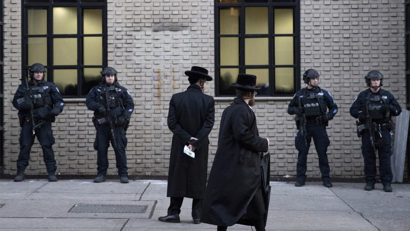 FILE - In this Dec. 11, 2019 file photo, Orthodox Jewish men pass New York City police guarding a Brooklyn synagogue prior to a funeral for Mosche Deutsch, a rabbinical student from Brooklyn who was killed in a shooting at a market in Jersey City, N.J. (AP Photo/Mark Lennihan, File)