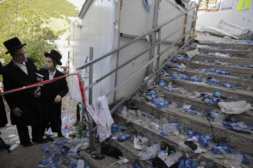 Ultra-Orthodox Jews look at the scene where fatalities were reported among the thousands of ultra-Orthodox Jews during the Lag b'Omer festival at Mount Meron in northern Israel, Friday, April 30, 2021. A stampede at the religious festival attended by tens of thousands of ultra-Orthodox Jews in northern Israel killed dozens of people and injured more than 100 others early Friday, medical officials said, in one of the country's deadliest civilian disasters. (AP Photo/Sebastian Scheiner)