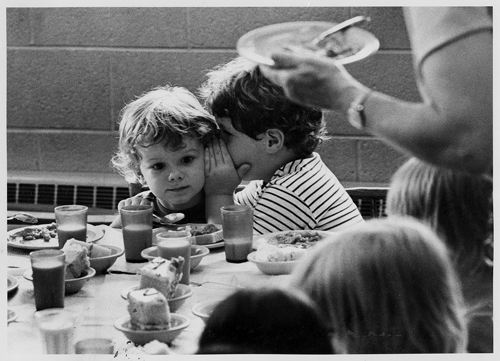 Three-year-old Jason Smith, left, listens to a secret from James Brady, 4, during lunch at a church-affiliated day care center near Detroit, in Oct. 1978. With the dramatic increase in the number of working mothers, similar operations are on the rise at congregations throughout the U.S. Often staffed by volunteers, they provide reliable, low-cost care for the children. RNS archive photo by Dwight Cendrowski. Photo courtesy of the Presbyterian Historical Society.
