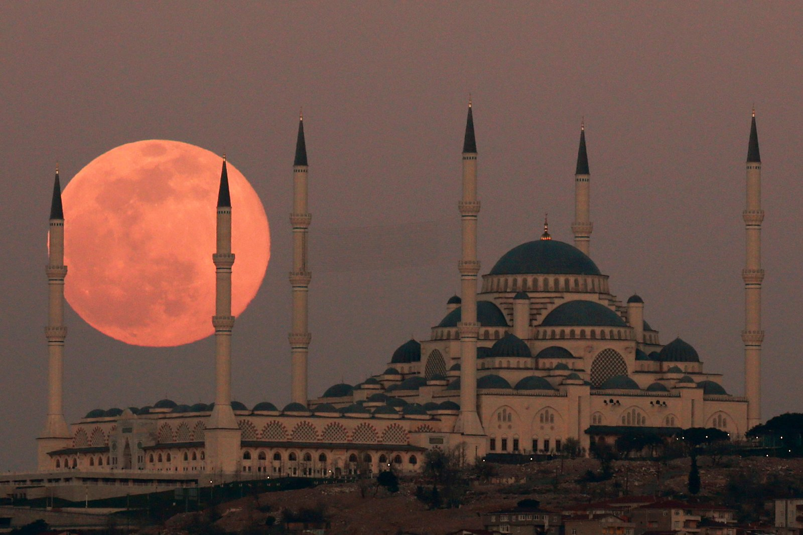 """The full moon rises Sunday, March 28, 2021, over the Camlica Mosque, the largest mosque in Asia Minor, in Istanbul. The March full moon is called the """"Worm Moon"""". (AP Photo/Emrah Gurel)"""